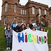 Crowds at Inverness Castle hold a banner for Qu...